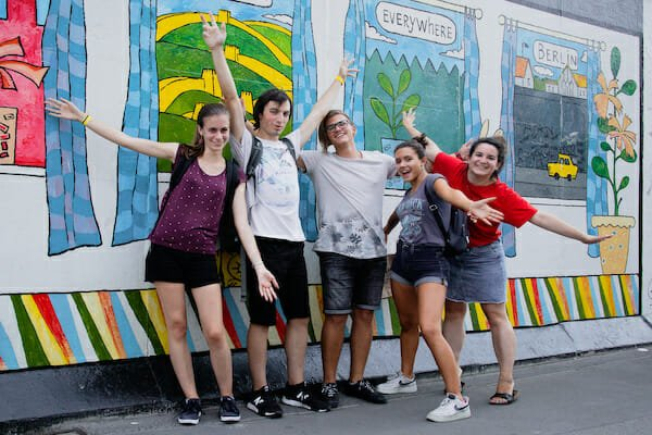 Students of the Berlin German Language School on a walking tour of Berlin in front of graffiti wall